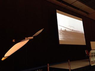 会場に飾られていた、今年の鳥人間コンテスト出場機のプロペラと、スクリーンに映し出される過去の日大の人力飛行機