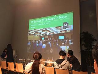 開演前の登壇席(IA Summit会場の写真がスクリーンに映し出されている)